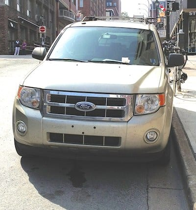 PARKED INCORRECTLY: Vehicle parked on steep hill with wheels parallel to the curb.