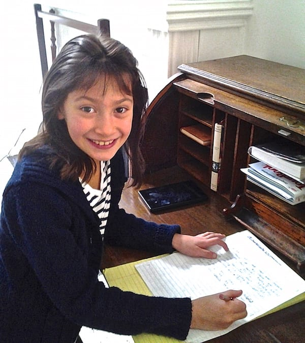 This image captures a young author busy writing her stories.