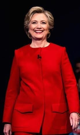 Democratic presidential candidate, Hillary Clinton, seen in her blood-red, ready for battle, hip trimming Ralph Lauren pantsuit.